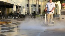 Crew pressure washing common area of shopping center