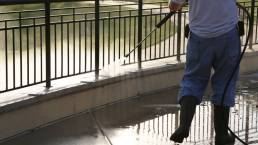 Man pressure washing ledge