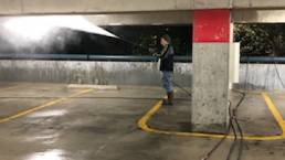 Crew pressure washing parking garage ceiling