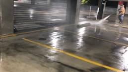 Crew pressure washing parking garage 2