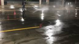 Crew pressure washing parking garage