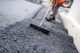 Worker leveling fresh asphalt