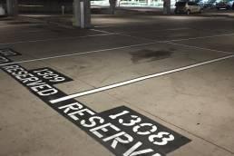 Striping reserve stencil in parking garage